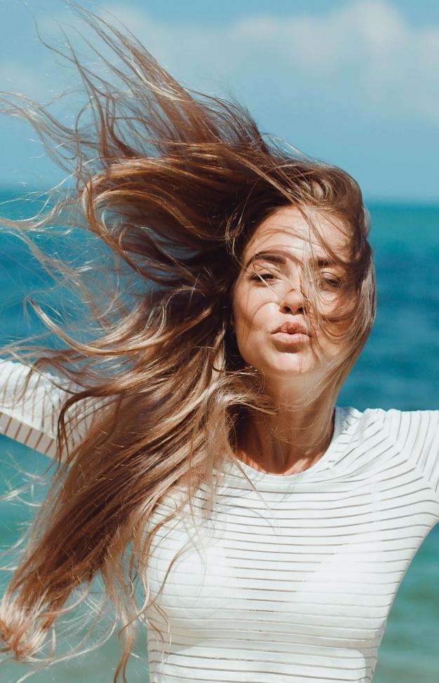 fille-donnant-un-baiser-avec-ses-cheveux-sur-son-visage_1296-111